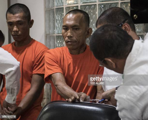 National Bureau of Investigations agents remove the handcuffs of suspected Islamist militants Hood Abdullah and Jimmy Bla during a press conference...