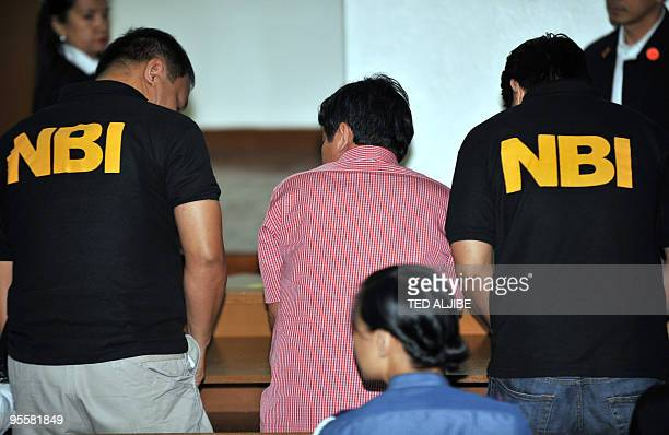 National Burueau Investigation agents escort Andal Ampatuan Jnr the prime suspect in the country's worst political massacre prepares to sit with NBI...