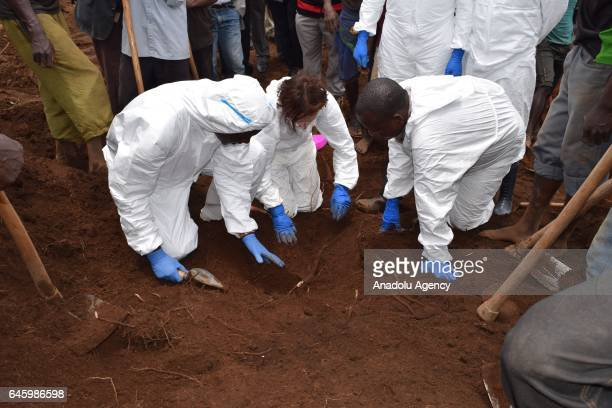National Commission for Truth and Reconciliation officials inspect remains of people at the mass grave existing from 1972 in Mwaro, Burundi on...
