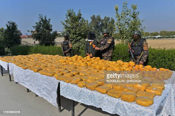 National Directorate of Security forces stand guard along with a detained suspect after bags containing Opium and Hashish were seized in an operation...