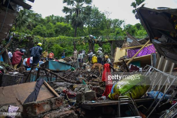 National Disaster Response Force and other rescue team personnel inspect the site of the landslide in a slum area where 18 people were killed after...