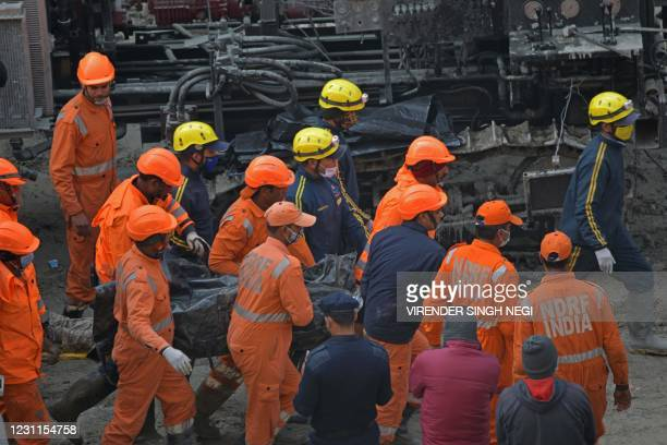 National Disaster Response Force crew carry the body of a victim following rescue efforts from Tapovan tunnel in Chamoli on February 14 after flash...