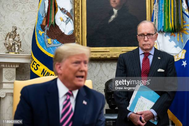 National Economic Council Director Larry Kudlow looks on as US President Donald Trump speaks to reporters in the Oval Office of the White House as he...