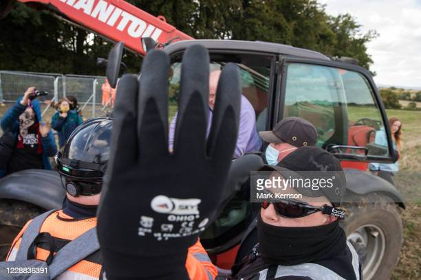 A National Eviction Team bailiff obstructs the photographers camera as a farmer in a telehandler positioned on land not compulsorily purchased by HS2...