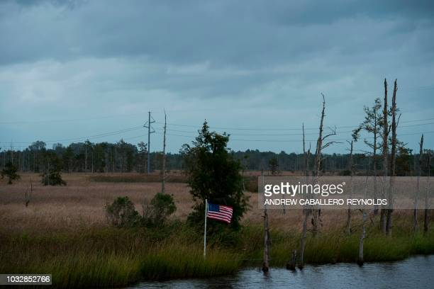 A US national flag flutters in the wind as hurricane Florence starts to make landfall in Lealand North Carolina on September 13 2018 Hurricane...