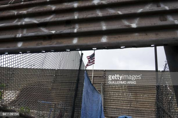 A US national flag hangs from the USMexico border fence in Tijuana Baja California northwestern Mexico on April 2 2018 President Donald Trump lashed...