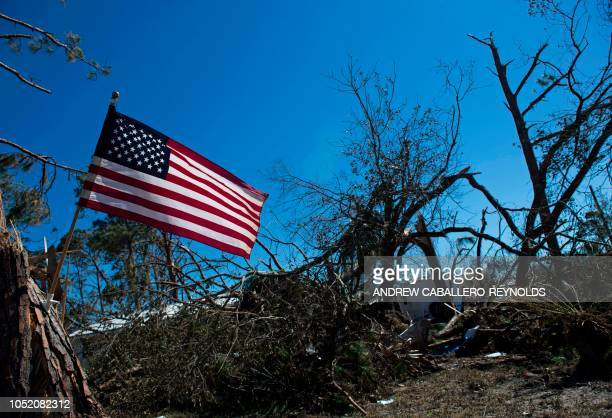 A US national flag hangs on a tree near a destroyed trailier in Port St Joe beach Florida on October 13 three days after hurricane Michael hit the...