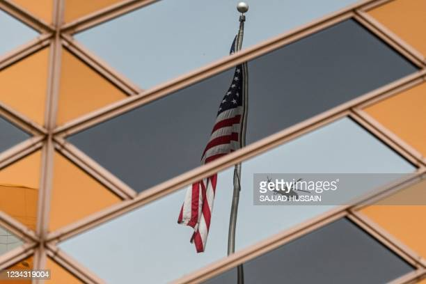 National flag is reflected on the windows of the US embassy building in Kabul on July 30, 2021.