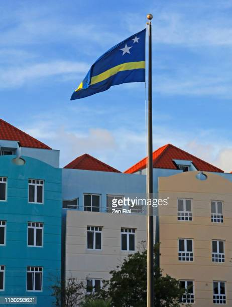 National flag of Curacao with pastel colored buildings in the background