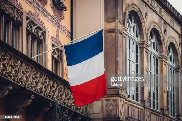 national flag of france on facade of historic building - franse vlag stockfoto's en -beelden