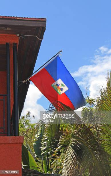 national flag of haiti on a flag pole attached to a building - haiti stock-fotos und bilder