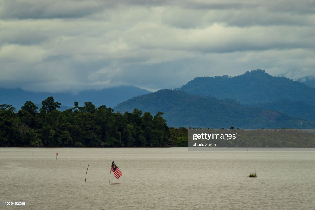 National flag of Malaysia or 'Jalur Gemilang' at lake Bukit Merah in Malaysia. : Stock Photo