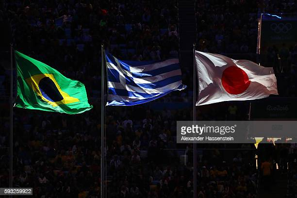 National flags of Brazil Greece and Japan are hoisted during the Closing Ceremony on Day 16 of the Rio 2016 Olympic Games at Maracana Stadium on...
