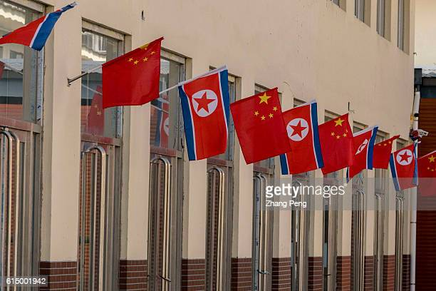 National flags of China and North Korea are decorated in SinoKorea bilateral trade market which is located at Guomen Bay in the Dandong New city and...