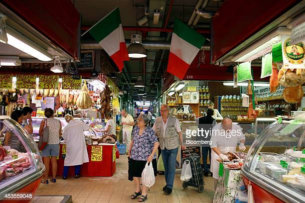 National flags of Italy hang above stalls as customers browse goods including meat and cheese at an indoor market in Rome Italy on Tuesday Aug 12...