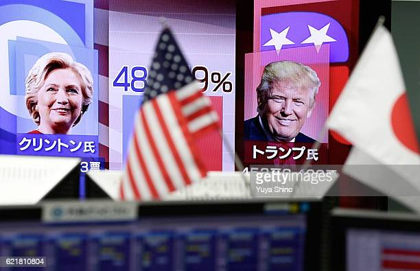National flags of the US and Japan are seen in front of a monitor displaying Democratic presidential nominee Hillary Clinton and Republican...