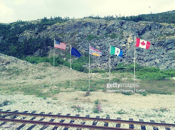 National Flags Waving Against Rocky Mountains