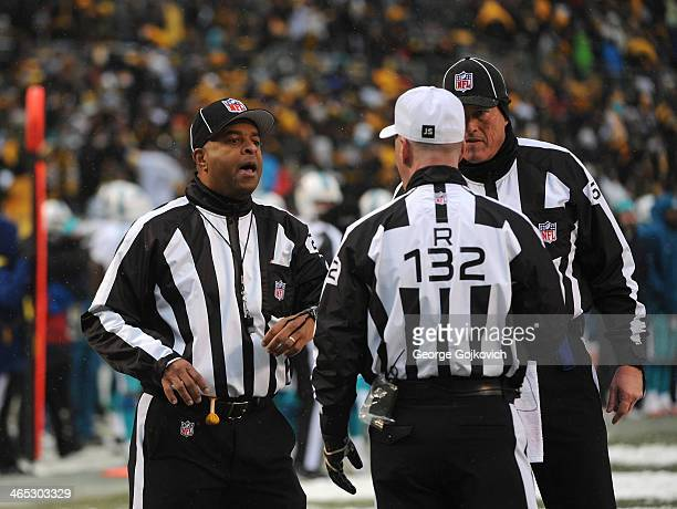 National Football League line judge Adrian Hill talks to referee John Parry and umpire Dan Ferrell during a game between the Miami Dolphins and...