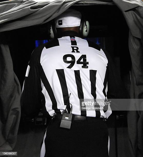 National Football League referee Mike Carey reviews a challenged play in the replay booth during a game between the New England Patriots and...