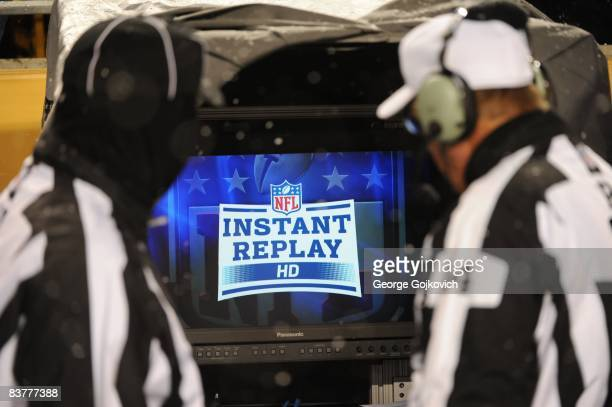National Football League referee Ron Winter and side judge Tom Hill look at the instant replay monitor on the sideline as snow falls during a game...