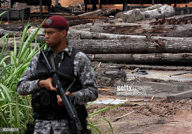 A National Force agent guards confiscated wood in a clandestine sawmill in the border of the Amazon rain forest 70 km from Tailandia Para in northern...