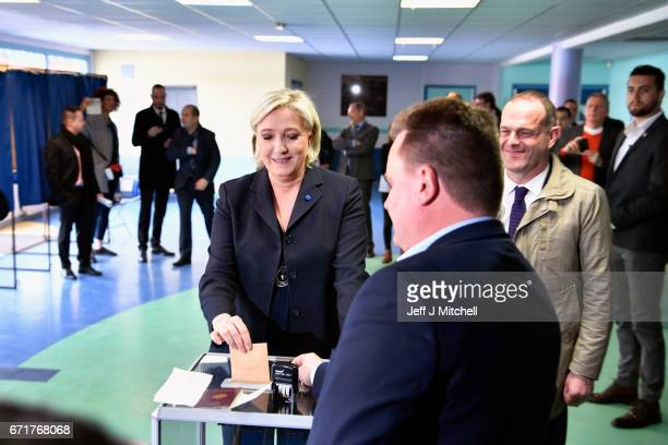 National Front Leader Marine Le Pen, casts her vote for the French elections into the ballot box at a polling station on April 23, 2017 in Henin...