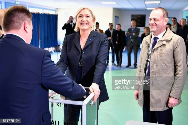 National Front Leader Marine Le Pen casts her vote for the French elections into the ballot box at a polling station on April 23 2017 in Henin...
