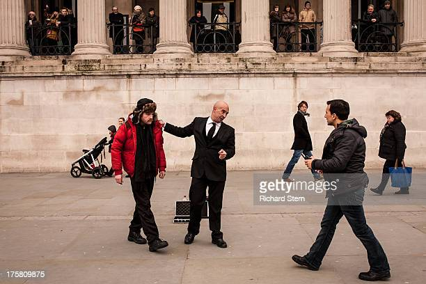 CONTENT] National Gallery incident mystery risk Five people young men macho real people interaction altercation urban scene Trafalgar Square serious...