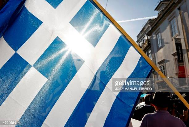 A national Greek flag is seen during a demonstration in support of Greece in Lisbon on July 4 2015 a day before nearly 10 million Greek voters take...
