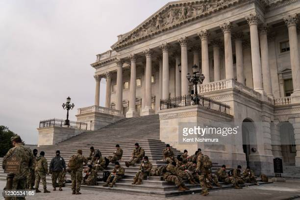 National Guard eat breakfast while sitting on the steps to the House of Representatives on the U.S. Capitol Building grounds, as heightened security...