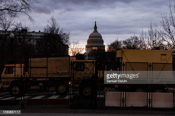 National Guard Family of Medium Tactical Vehicles and security fencing block a road to the U.S. Capitol on the morning of January 17, 2021 in...