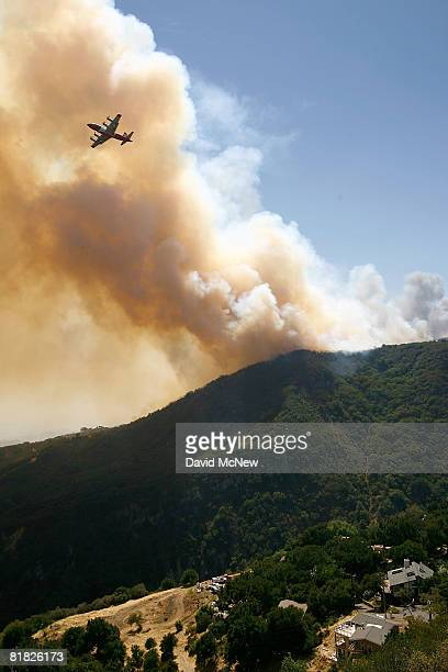National Guard firefighting airtanker drops PhosCheck fire retardant in an attempt to prevent the Gap fire from reaching homes that were rebuilt...