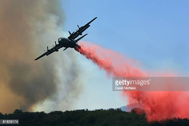 National Guard firefighting airtanker drops PhosCheck fire retardant over the Gap fire as more than 1000 wildfires continue burning across about 680...