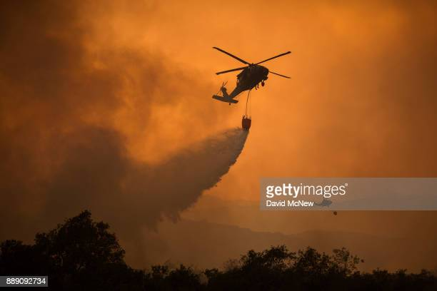 National Guard helicopters make water drop as the Thomas Fire approaches the Lake Casitas area on December 9 2017 near Ojai California Strong Santa...