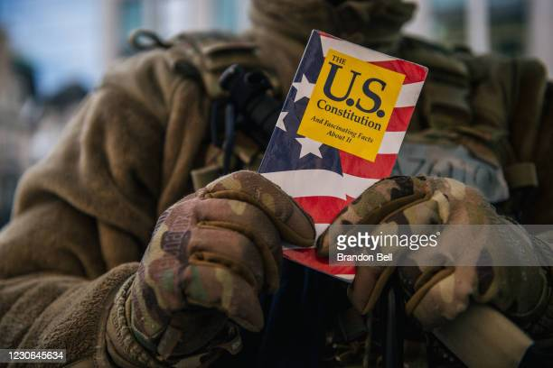 """National Guard Master Sergeant George Roachs holds up a pamphlet of the U.S. Constitution on January 17, 2021 in Washington, DC. """"It's hard for me to..."""