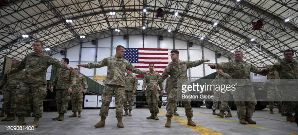 National Guard members stand six feet apart to socially distance after a New England Patriots jet arrived at Logan Airport in East Boston on Apr 1...