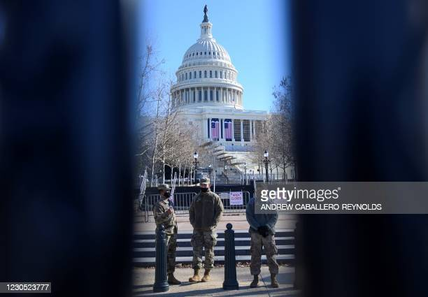National Guard monitor a walkway behind a fence near the US Capital in Washington, DC on January 20, 2021. - Donald Trump faced fresh calls Sunday...