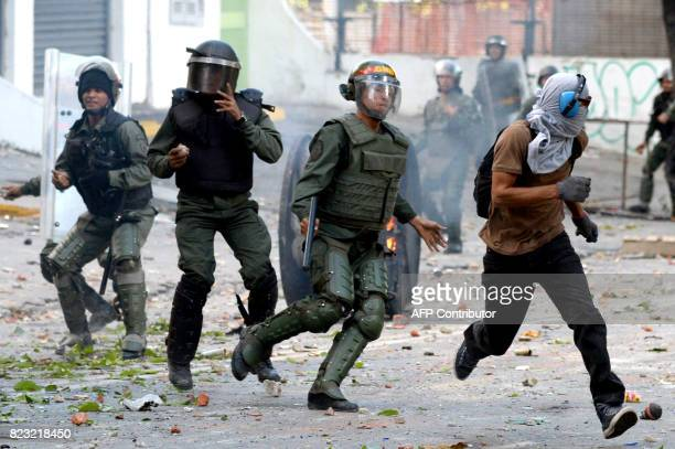 National Guard personnel in riot gear chase a demonstrator during clashes ensuing an anti-government protest in Caracas, on July 26, 2017....
