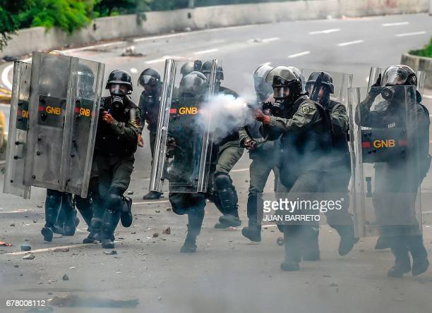National Guard personnel in riot gear fire year gas grenades and charge on opposition activists during a protest against Venezuelan President Nicolas...