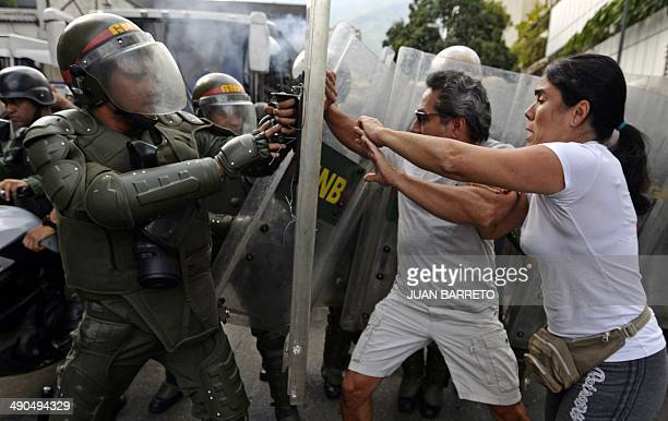 National Guard personnel in riot gear struggle with antigovernment demonstrators during a protest in Caracas on May 14 2014 About 80 demonstrators...