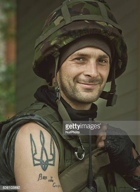 National Guard soldier with trident - Ukrainian national symbol - tattoo on his shoulder patrols at a check point near Slaviansk . Ukrainian army...