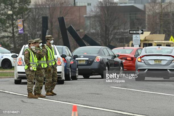 National Guard soldiers are seen stationed at the entrance of the new drive through COVID-19 testing facility at Bergen Community College on March...