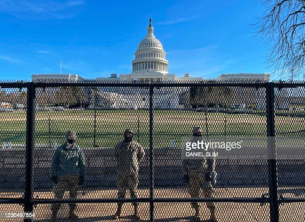 National Guard soldiers guard the grounds of the US Capitol from behind a security fence in Washington, DC, on January 9, 2021. - US Democrats on...
