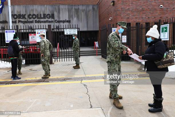 National Guard soldiers help people at the York College coronavirus vaccination site on February 24, 2021 in the Jamaica neighborhood of Queens...