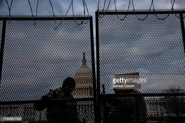National Guard soldiers secure a gate to the east front of the U.S. Capitol on the morning of January 17, 2021 in Washington, DC. After last week's...