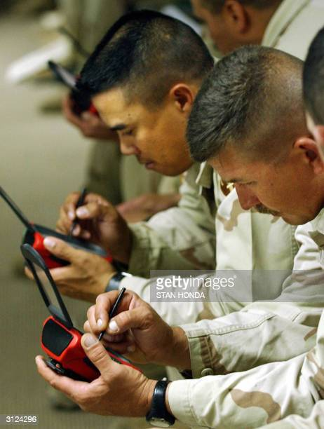 National Guard soldiers Sgt Ian Bodrov and Staff Sgt Norm Betron of the 257 Transportation Company from Las Vegas NV enter data on a handheld...