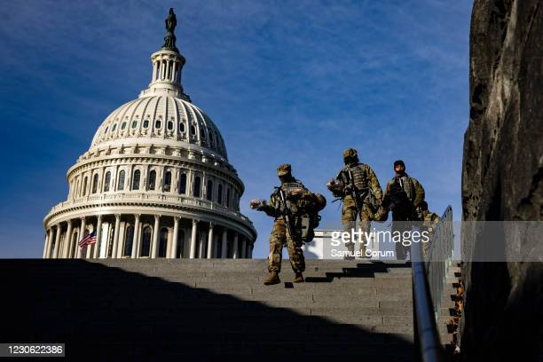 National Guard soldiers walk down the steps to the Capitol Visitors Center with the U.S. Capitol dome behind them on the east front of the U.S....