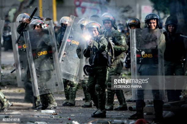 National Guard trooper in riot gear fires his shotgun at opposition demonstrators during clashes ensuing an antigovernment protest in Caracas on July...