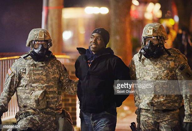 National Guard troops assist police in arresting demonstrators during a protest in front of the police station on November 25 2014 in Ferguson...