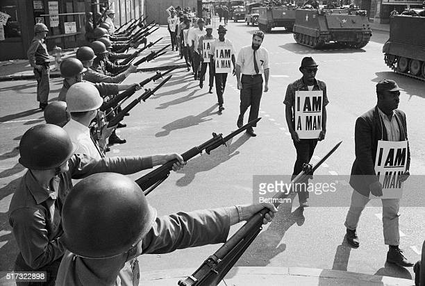US National Guard troops block off Beale Street as Civil Rights marchers wearing placards reading I AM A MAN pass by on March 29 1968 It was the...